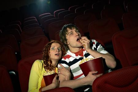 impassive: Young girl sitting terrified at cinema hall, her impassive boyfriend eating popcorn Stock Photo