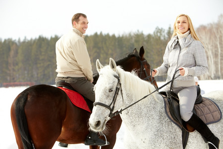 Portrait of happy family horseback riding in winter