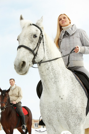 A man and a woman riding horses outside, low angle
