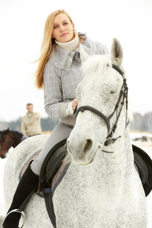 Brave beautiful woman going on a horseback outside