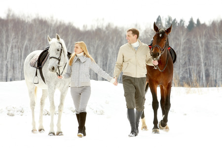 dapple grey: A young couple leading their horses with reins