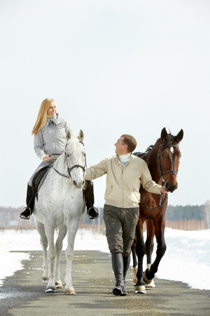 A woman and a man dating and riding horses