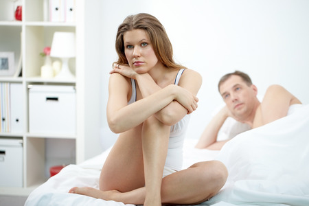 adultery: A young woman sitting on bed upset with her lying husband near by