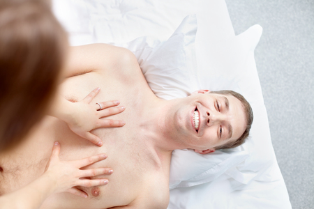 sexual foreplay: Woman stroking her happy man lying on bed, above veiw Stock Photo