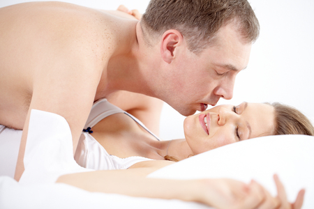 passionate lovers: A man lying over his girlfriend and stroking her