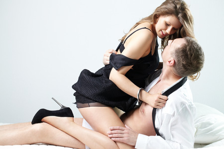 enamorados en la cama: Una mujer joven que tienta a un hombre en la cama