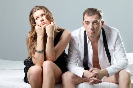 adultery: A husband and wife sitting on bed displeased not looking at each other