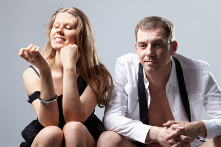 impotence: Portrait of two half-dressed valentines sitting confused on bed