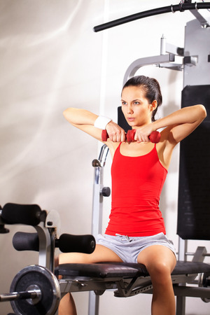 exercise machine: A young girl sitting on exercise machine and lifting dumbbells Stock Photo
