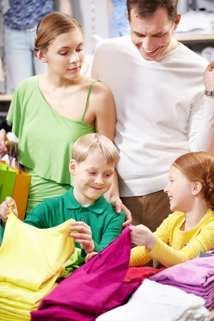 choosing clothes: Parents with two children looking for child clothing in the shop Stock Photo