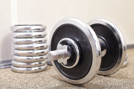 adjustable dumbbell: Close-up of a dumbbell with weight plates Stock Photo