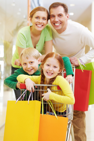 Two parents with their child in shopping cart looking at camera and smiling Imagens