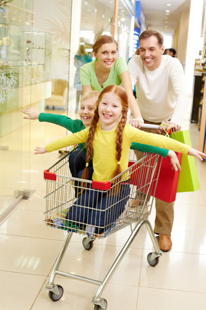 shopping cart: Two parent carrying their child in shopping cart Stock Photo