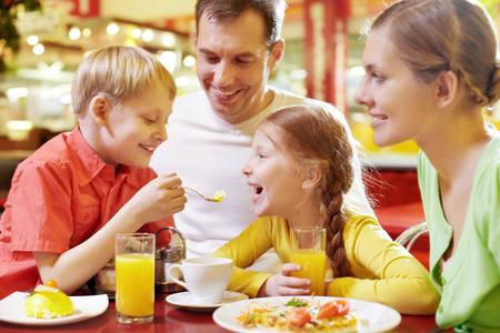 Rodina se dvěma dětmi sedí v kavárně, chlapec krmí svou sestru lžící