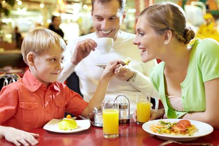 Familia con un niño sentado en la cafetería, el niño alimentar a su madre con la cuchara