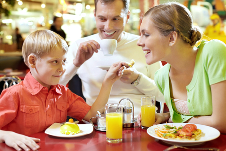 Family with one child sitting in cafe, the boy feeding his mother with spoon Stock Photo