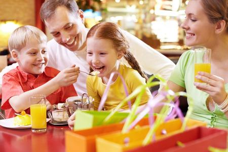 Familia de cuatro sentado en el café y comer, el hermano que introduce a su hermana