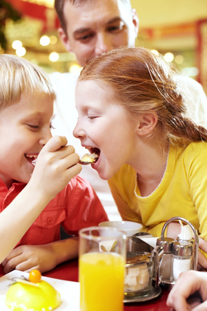 A little boy feeding his sister with a spoon in cafe