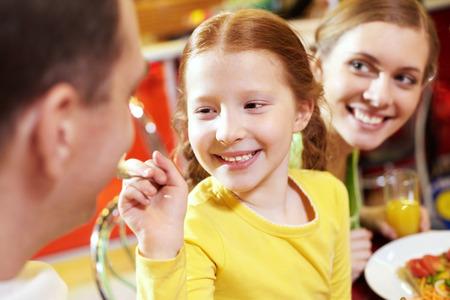 Close-up von einem kleinen Mädchen, das ihr Vater mit dem Löffel füttern und lächelnd