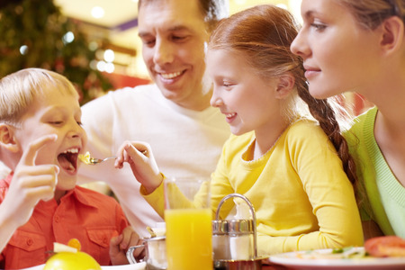 A family of four sitting in cafe, the girl feeding her brother with a spoon photo