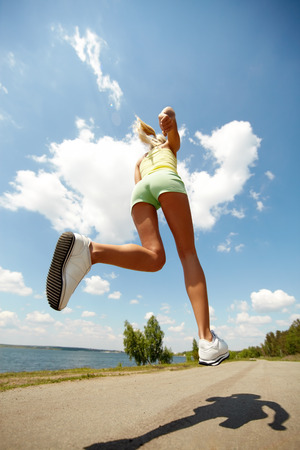 energetically: Rear view of a girl jogging energetically