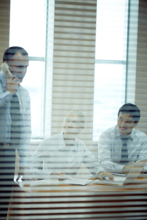 Three people working in office viewed through jalousie photo