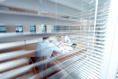Three busy business people working in office viewed through jalousie Stock Photo