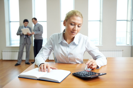 Female accountant working in office with business people in the background photo