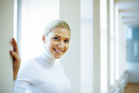 Portrait of beautiful woman looking at camera and smiling in office photo