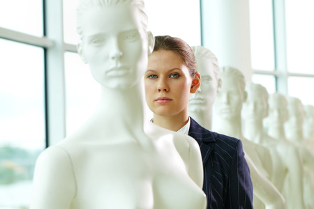 intimidating: A young woman standing in line with mannequins