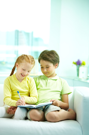 Two children sitting on sofa together and writing Stock Photo