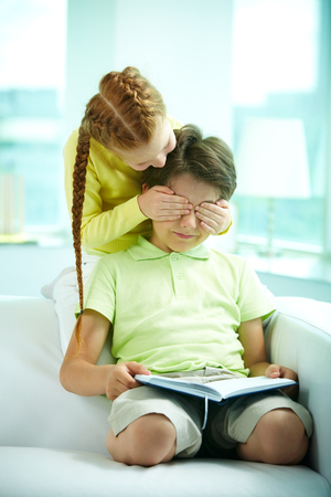 Little girl closing her brother s eyes while he is reading a book photo