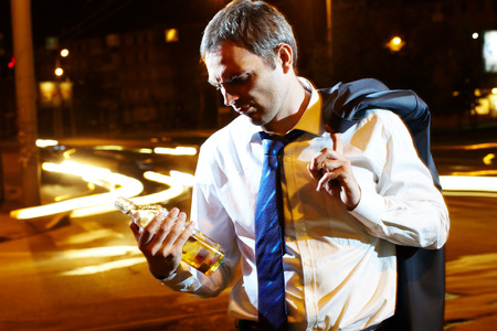 unwinding: Portrait of a businessman with a bottle of whisky at night