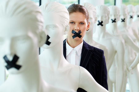 A woman standing in line of mannequins with taped mouth Stock Photo