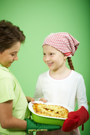 A little girl showing to a boy a pie cooked by herself photo