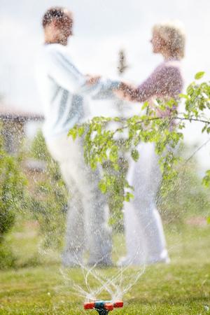 Playful couple through sprinkler splashes