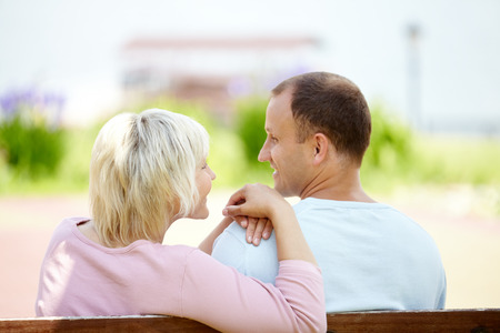 long lasting: Rear view of a mature couple sitting on bench