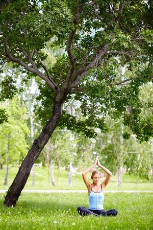 A girl meditating under a tree photo