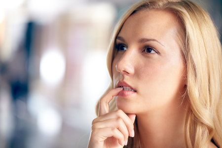 Face of a beautiful woman looking away in doubt photo