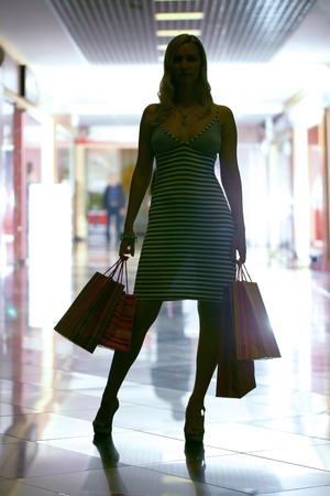 Silhouette of a woman standing in shopping center photo