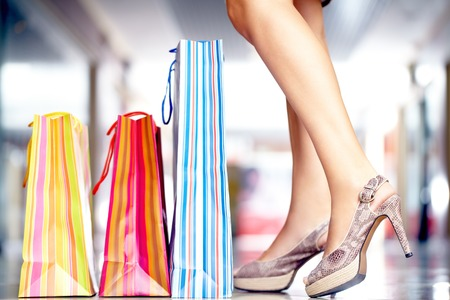 Three shopping bags at slim female legs in high-heeled shoes