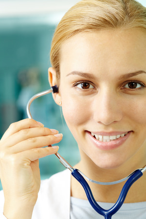 Portrait of a pretty nurse with stethoscope looking at camera and smiling photo