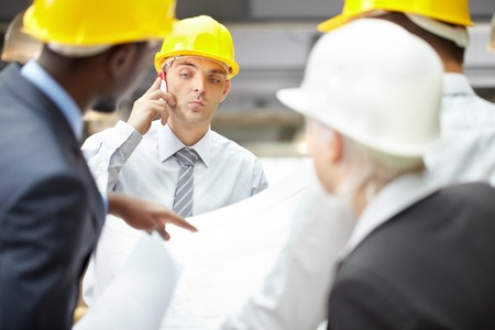 Young architect talking on the phone among his colleagues photo