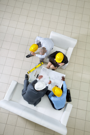 Above view of four engineers sitting at table and planning a housing project photo