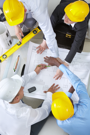 High angle view of four engineers discussing a housing project photo