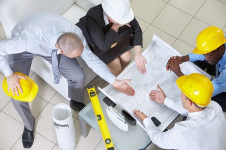 Four engineers sitting at table and discussing a blueprint photo