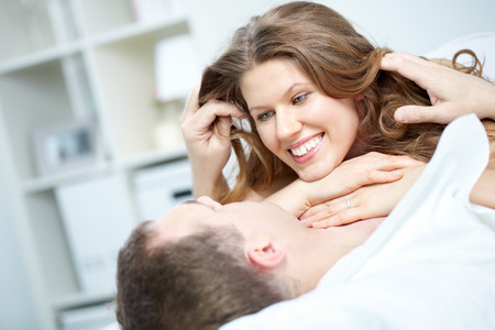 A young woman lying on her boyfriend in bed and the man stroking her hair Stock Photo