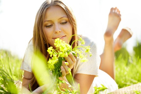 girl lying: A beautiful girl lying on grass with flowers