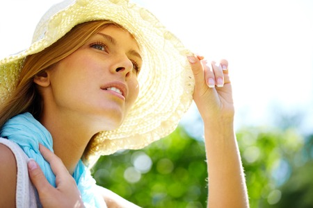 Portrait of a woman sitting in summer hat photo