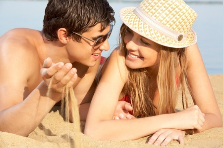 Portrait of a young couple lying on sand and looking at each other